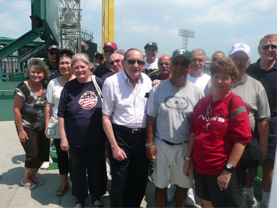 "Travelers sat in the Green Monster seats to see the park from a very unique point. During the tour, travelers stopped for a group picture. The yellow pole in the back left is the famous Carlton ""Fisk Pole."""